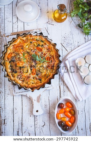 Delicious homemade ricotta pie with mushroom, chicken and tomato cherry over on a decorative rustic cutting board from above on kitchen table with colorful tomato and green leaves. see series - stock photo
