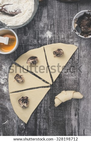 Delicious homemade rolls with nougat creme. Photographed from above on rustic wooden table. Processed to mach old film look. - stock photo