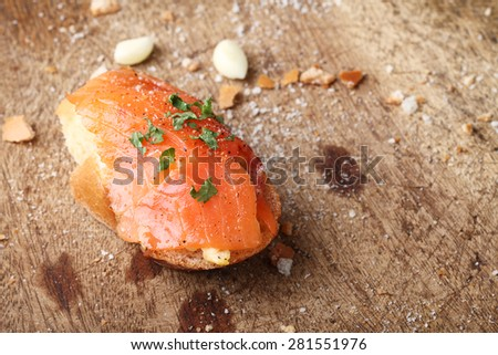 Delicious homemade scrambled eggs with smoked salmon garnished with a fresh parsley leaf on rustic wood - stock photo