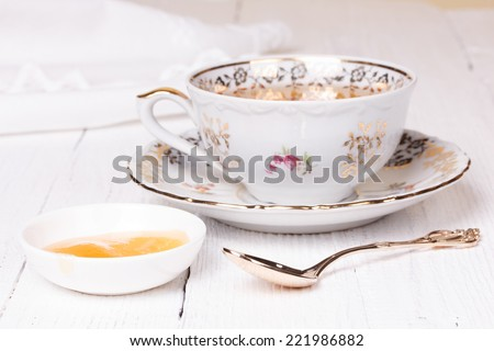 delicious honey and antique cup with tea - stock photo
