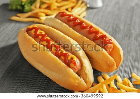 Delicious hot-dog with French fries and vegetables on wooden background