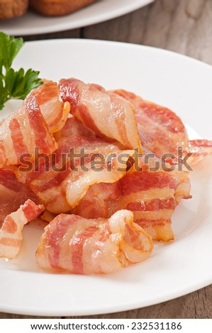 delicious hot fried bacon on a white plate - stock photo