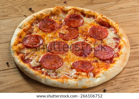 Delicious hot pizza pepperoni with different spices on wooden table ready to eat - stock photo