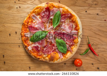 Delicious hot pizza with bacon, tomatoes, cheese and different spices on wooden table ready to eat - stock photo