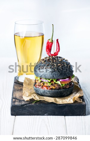Delicious hot spicy black burger with chili pepper on craft paper and glass of beer on cutting board on white wood table - stock photo