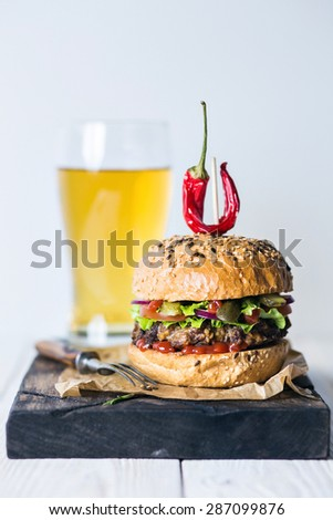 Delicious hot spicy burger with chili pepper and glass of beer on craft paper on cutting board on white wood table - stock photo