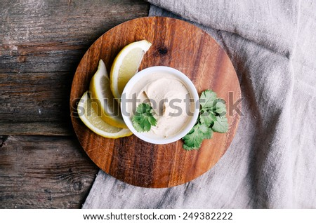 Delicious hummus on the wooden table - stock photo