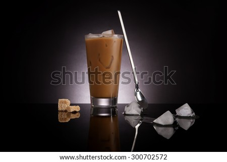 Delicious ice coffee with melting ice cubes and brown sugar on dark background. Culinary gourmet luxurious coffee drinking. - stock photo