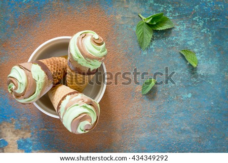 Delicious ice cream cone with mint and chocolate on a vintage wooden background. Top view . - stock photo