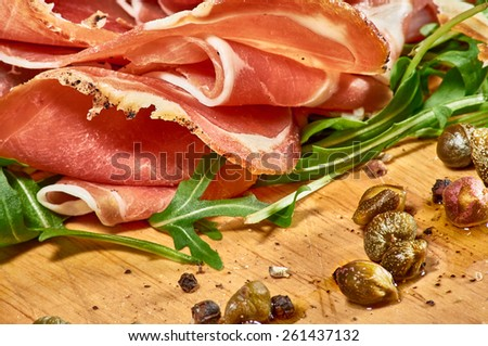 Delicious Indigenous Croatian prosciutto ham lying on rucola with capers on a wooden platter - stock photo