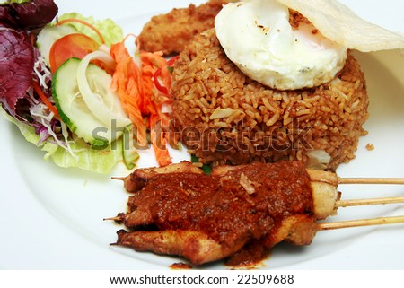 Delicious Indonesian Nasi Goreng with prawn crackers and chicken satay - stock photo