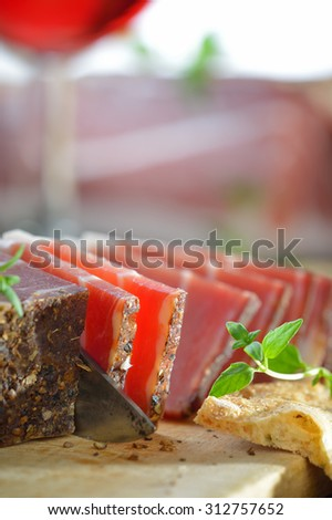 Delicious Italian bacon from South Tyrol with crispy flat bread an a glass of red wine - stock photo