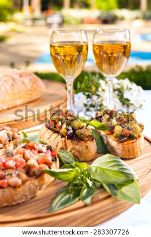 Delicious italian bruschetta with tomatoes, basil and glasses of white wine - stock photo