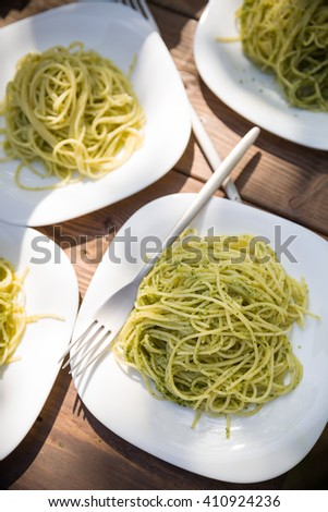 Delicious Italian pasta with green pesto. Spaghetti with homemade basil pesto sauce. Healthy dinner or lunch. Homemade food on wooden table background - stock photo