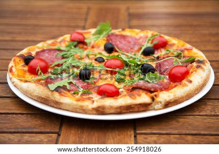 Delicious italian pizza served on wooden table closeup