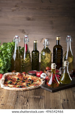 Delicious italian pizza served with chili flavored olive oil on wooden table