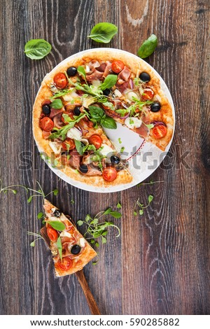 Delicious italian pizza with prosciutto served on wooden table