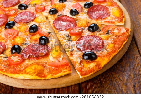 Delicious italian pizza with salami pepperoni, mushrooms and black olives - thin pastry crust at wooden table background - stock photo