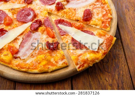 Delicious italian pizza with salami, sausages, bacon, parmesan and cherry tomatoes - thin pastry crust at wooden table background - stock photo