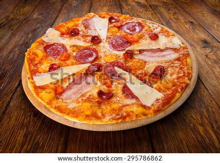 Delicious italian pizza with salami, sausages, bacon, parmesan and cherry tomatoes - thin pastry crust at wooden table background on wooden desk - stock photo