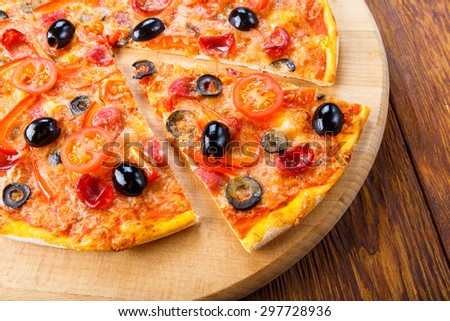 Delicious italian pizza with sausages and black olives - thin pastry crust at wooden table background on wooden desk - stock photo