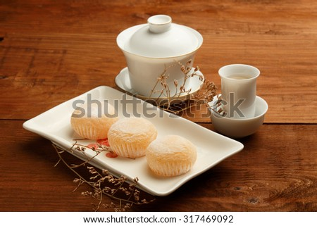 Delicious japanese mochi rice cakes on white plate, gaiwan and white porcelain cups with green tea standing on brown wooden surface decorated with dried flower. Shallow dof. Focus on first cake. - stock photo