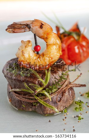 Delicious juicy barbecued steak and prawns with grilled tomato. Surf and Turf style. - stock photo