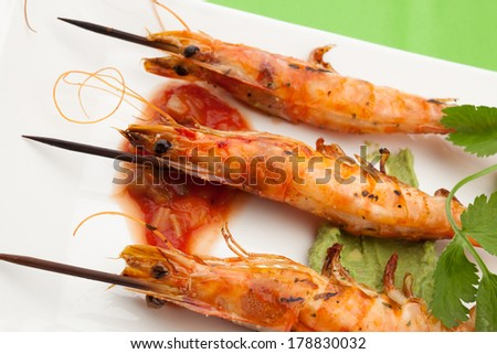 Delicious large spicy grilled whole shrimps -scampi- with salsa and guacamole sauces and fresh cilantro.  - stock photo