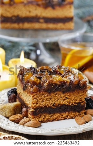 Delicious layer gingerbread cake decorated with dried fruits - stock photo