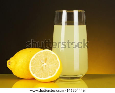 Delicious lemon juice in glass and lemons next to it on dark orange background - stock photo