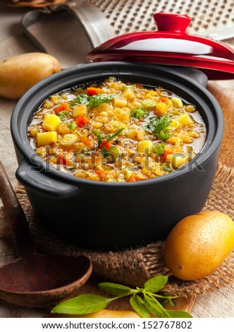 Delicious lentil and vegetable stew in a rustic kitchen in an open crock, high angle view - stock photo