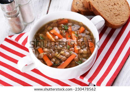 Delicious lentil soup on table close-up - stock photo