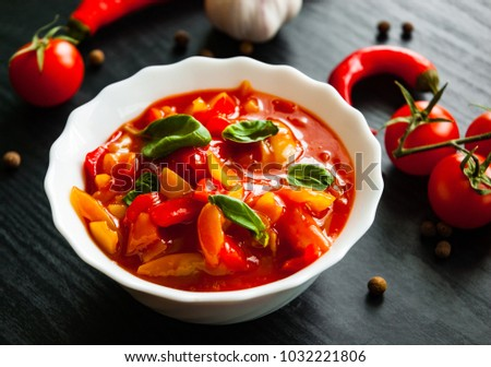 Delicious letcho with fresh vegetables in bowl on dark wooden background