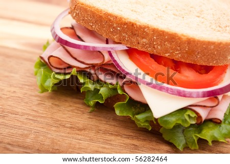 Delicious looking ham sandwich on cutting board - stock photo