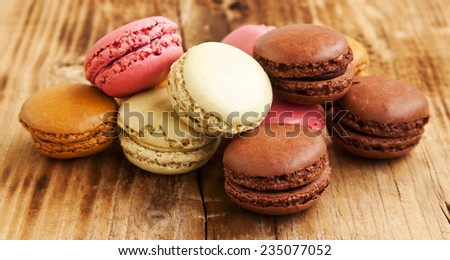 Delicious Macarons, French Pastry Cookies with Cream on Wooden Board
