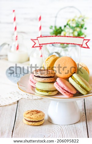 Delicious macarons on a cake stand with decorative name tag. - stock photo