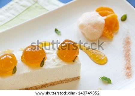 Delicious mandarin cheese cake with mandarin balls and a fruit sauce. - stock photo