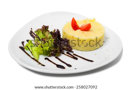 Delicious mashed potatoes with tomatoes and lettuce. Isolated on a white background.