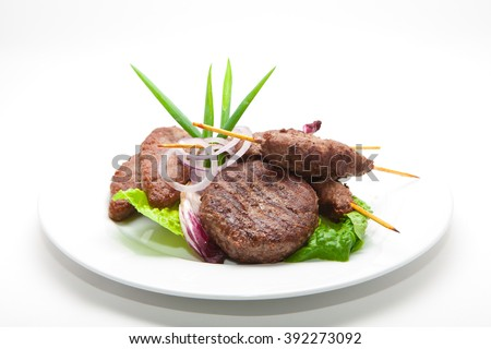 Delicious meat cutlets and steak On a White Background.Skewered on wooden sticks tasty pork meat - stock photo