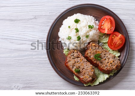 Delicious meat loaf with rice on a plate on the table, a horizontal top view  - stock photo
