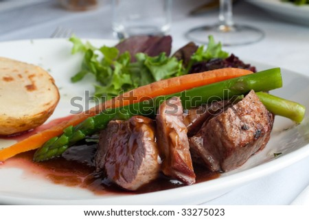 delicious meat pieces with soya sauce, carrot, asparagus and potato served on the plate - stock photo