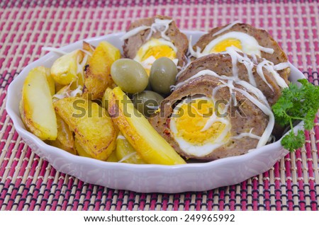 Delicious meatloaf, potato and olives on a restaurant dining table - stock photo