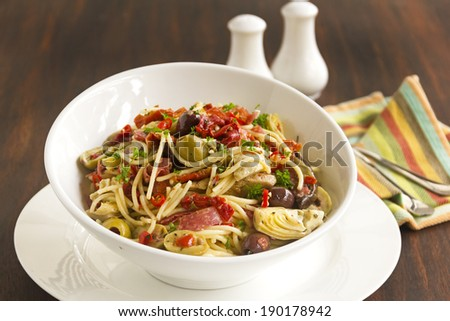 Delicious Mediterranean salami spaghetti with assorted vegetables ready to serve. - stock photo