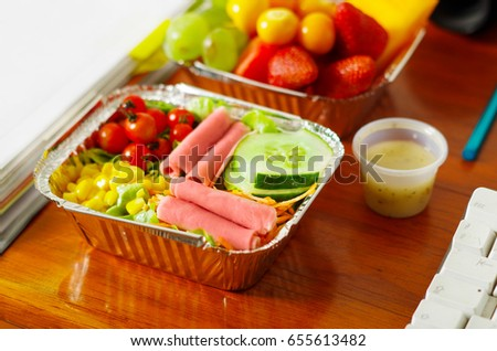 Delicious mediterranean-Style fresh salad with ham and blurred fruit salad on aluminium box on wooden table