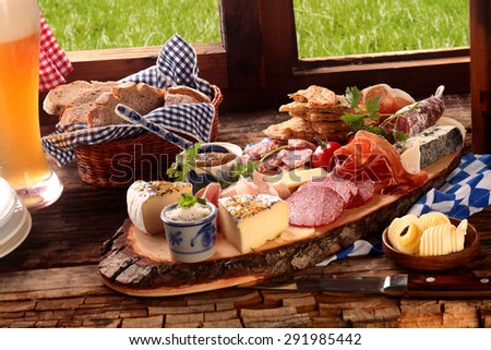 Delicious midday meal of a meat and cheese platter with a wide variety of cheeses, spicy sausage and ham served with a cold beer and fresh bread in a Bavarian tavern - stock photo