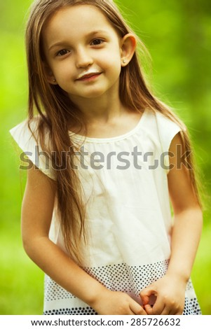 Delicious milk products concept. Funny portrait of sweet little girl smiling in beige dress with long brown hair posing in park. White moustache of yougurt on face. Outdoor shot - stock photo