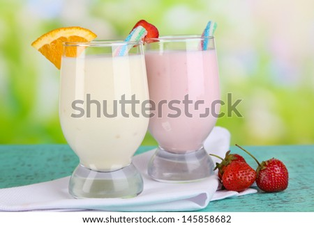 Delicious milk shakes with orange and strawberries on wooden table on natural background