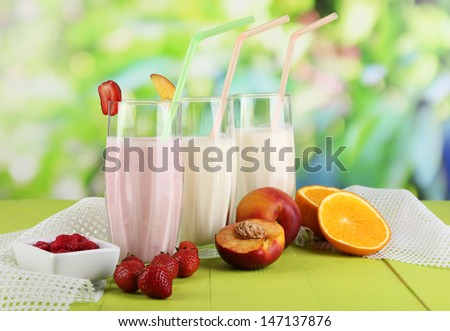 Delicious milk shakes with strawberries and peach on wooden table on natural background - stock photo