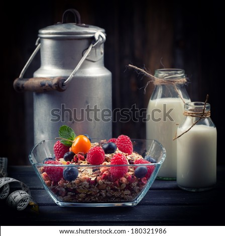 delicious muesli/cereal with fruits in a bowl and rustic milk bottles in Background, diet concept, dark background  - stock photo