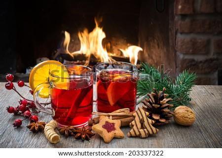 Delicious mulled wine with christmas decoration at romantic fireplace - stock photo